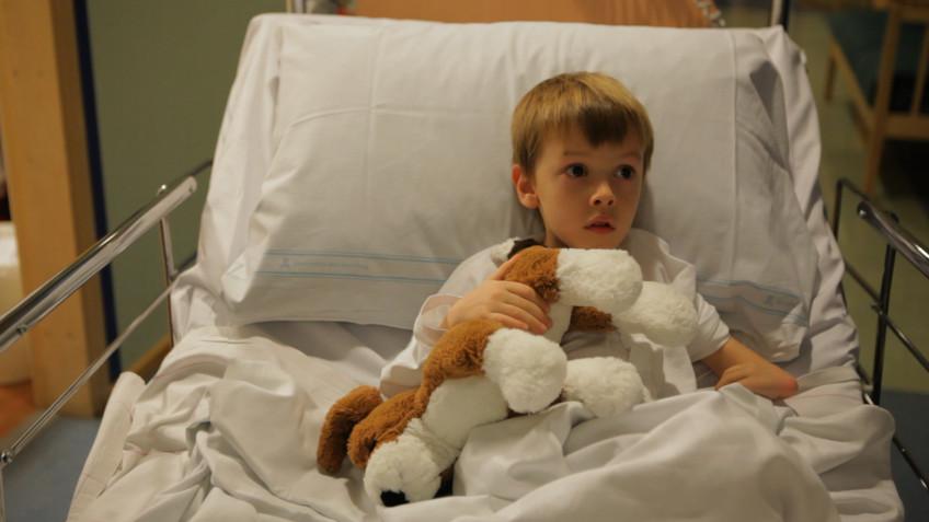 pojke i sjukhussäng ur clownmedicin på Astrid Lindgrens barnsjukhus Karolinska